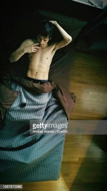 High Angle View Of Shirtless Mature Man Lying On Bed At Home