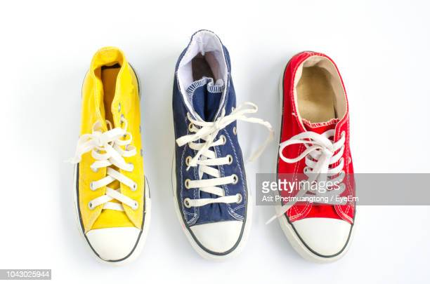 high angle view of shoes against white background - yellow shoe stock pictures, royalty-free photos & images