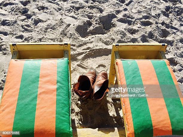 High Angle View Of Shoes Amidst Empty Lounge Chair At Beach