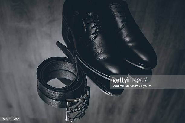 High Angle View Of Shoes And Belt On Table