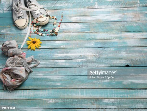 high angle view of shoes and flowers on floorboard - floorboard stock photos and pictures