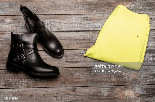 high angle view of shoes and pants on table - yellow trousers stock pictures, royalty-free photos & images