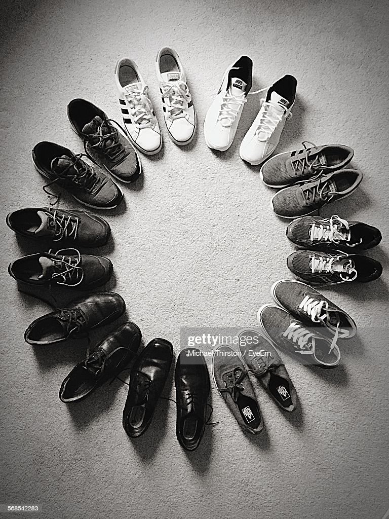 High Angle View Of Shoes Arranged In Circle On Floor : Stock Photo