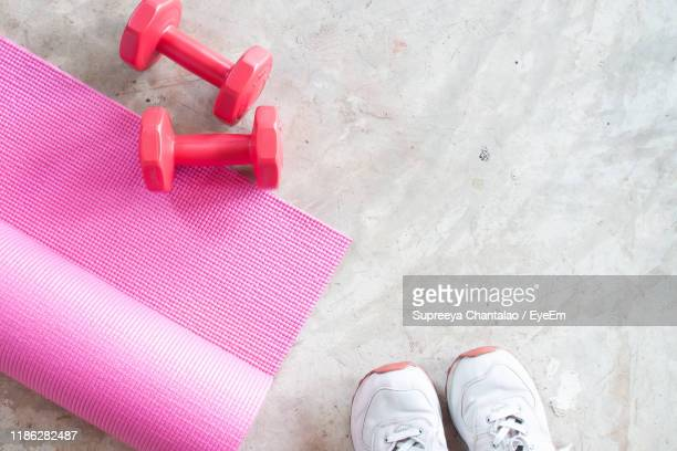high angle view of shoes by mat and dumbbells on floor - エクササイズマット ストックフォトと画像
