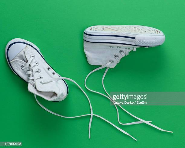 high angle view of shoes green background - chaussures blanches photos et images de collection