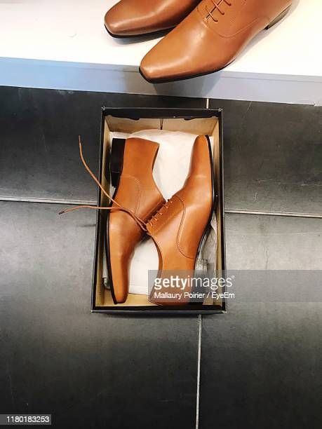 high angle view of shoes in box on tiled floor - chaussures en cuir photos et images de collection