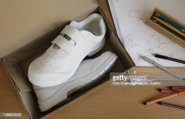 high angle view of shoes in cardboard box on wooden table - white shoe stock pictures, royalty-free photos & images