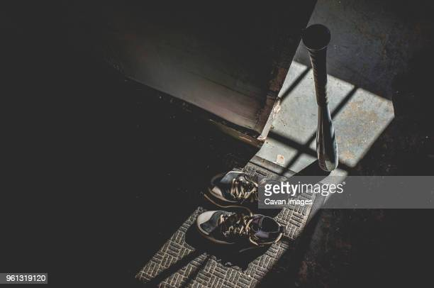 high angle view of shoes on doormat by baseball bat at home - baseball bat stock pictures, royalty-free photos & images
