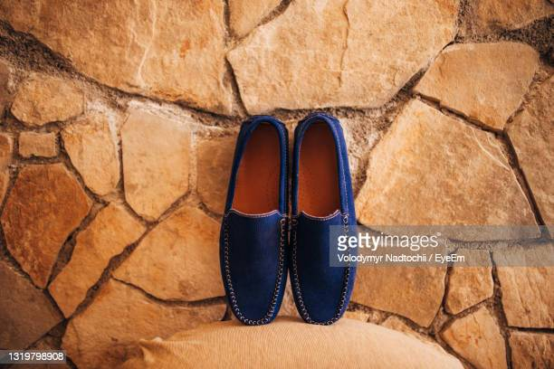 high angle view of shoes on footpath - lino stock pictures, royalty-free photos & images