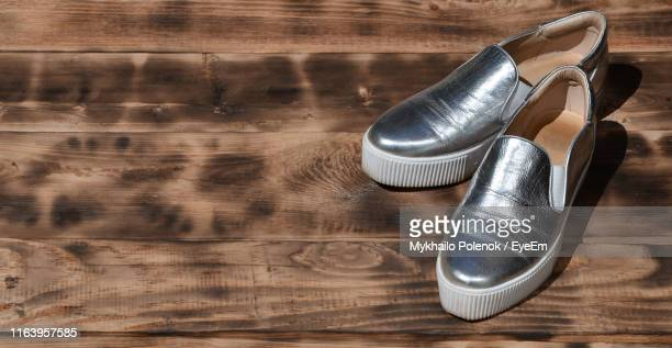 high angle view of shoes on hardwood floor - silver shoe stock photos and pictures