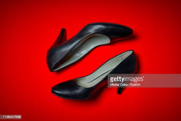 high angle view of shoes on red background - black shoe stock pictures, royalty-free photos & images
