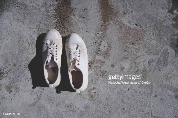 high angle view of shoes on sand at beach - chaussures blanches photos et images de collection