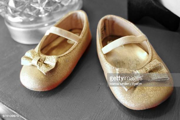 high angle view of shoes on table - gold shoe stock photos and pictures