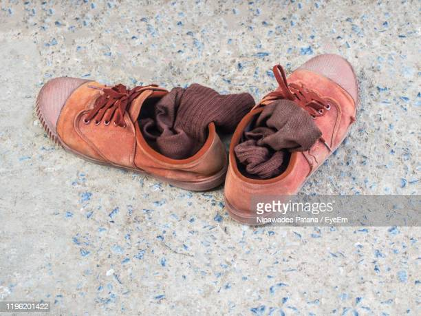 high angle view of shoes on tiled floor - pair stock pictures, royalty-free photos & images