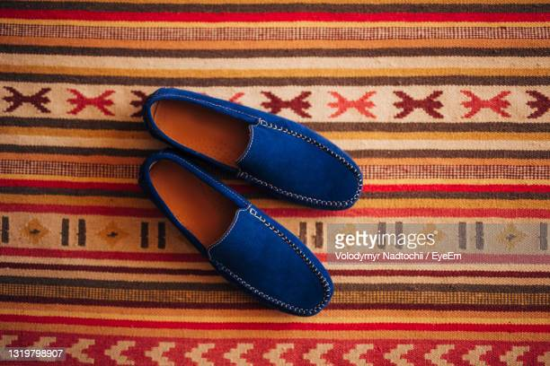 high angle view of shoes on tiled floor - lino stock pictures, royalty-free photos & images