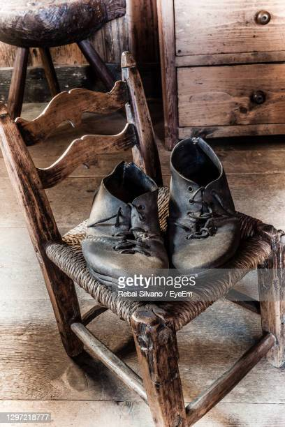 high angle view of shoes on wooden chair at home - rebai silvano foto e immagini stock