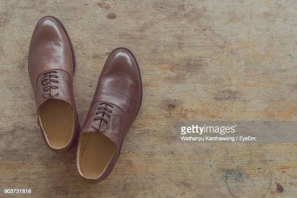 high angle view of shoes on wooden table - レザー・シューズ ストックフォトと画像