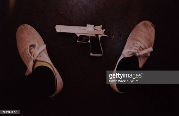 High Angle View Of Shoes With Gun On Floor