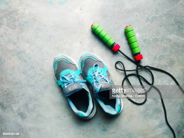 high angle view of shoes with jumping rope on floor - sportschuh stock-fotos und bilder