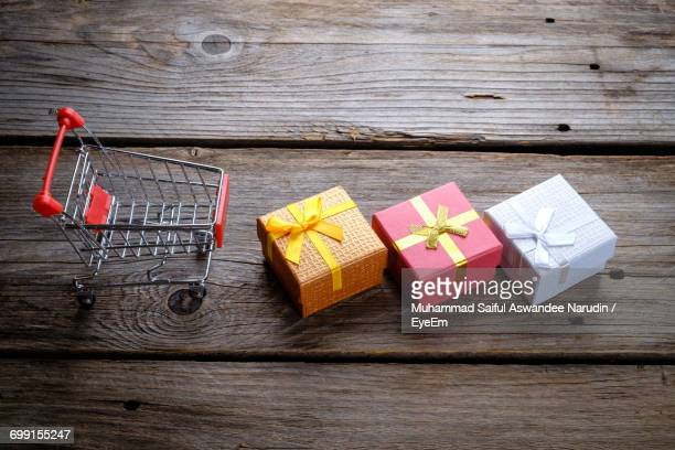 High Angle View Of Shopping Cart By Christmas Gifts On Wooden Table