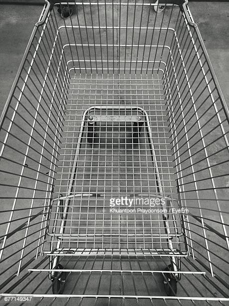 high angle view of shopping cart in parking lot - shopping trolley stock pictures, royalty-free photos & images