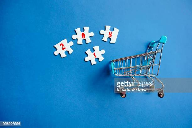 High Angle View Of Shopping Cart With Jigsaw Pieces On Blue Background