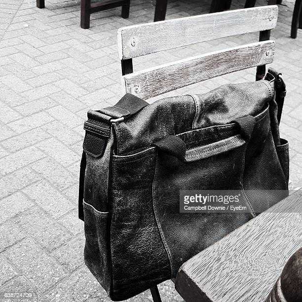 high angle view of shoulder bag on chair against footpath - campbell downie stock pictures, royalty-free photos & images