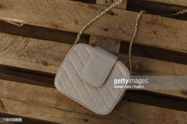 high angle view of shoulder bag on wooden footpath - shoulder bag stock pictures, royalty-free photos & images