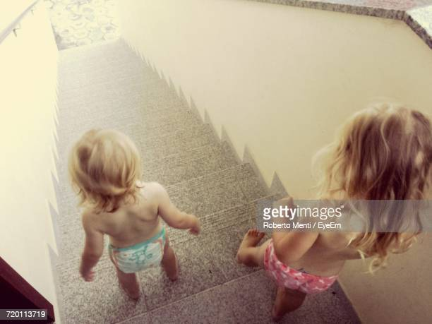 High Angle View Of Siblings Climbing Down Stairs