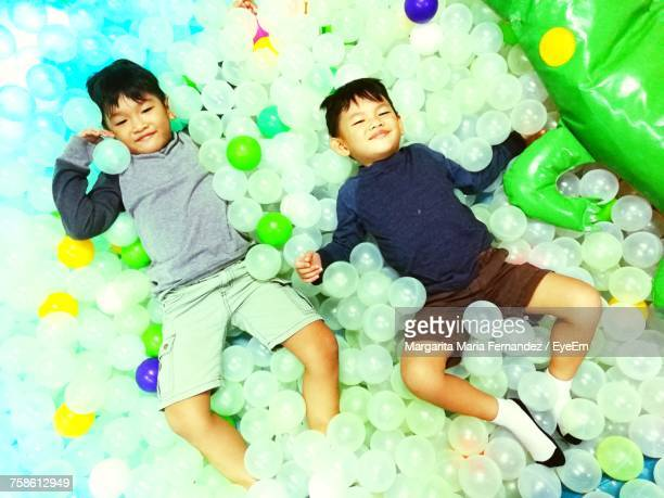 high angle view of siblings lying on ball pool - margarita seven photos et images de collection