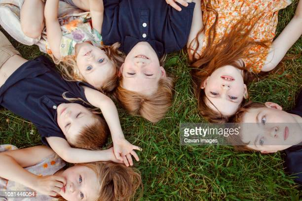 High angle view of siblings lying on grassy field