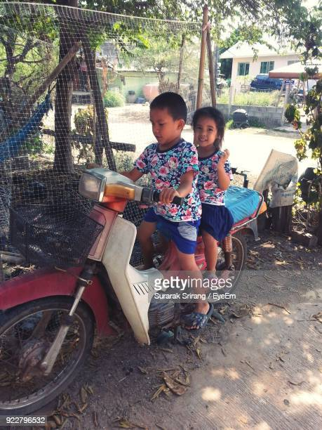High Angle View Of Siblings Riding Motorcycle