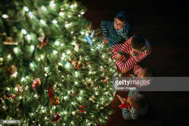High angle view of siblings sitting by Christmas tree at home