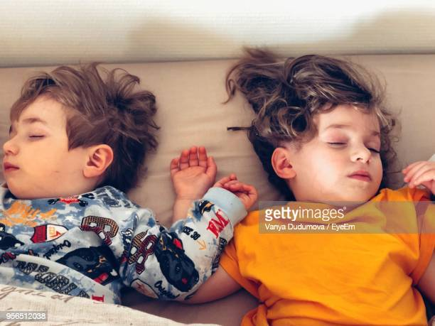 High Angle View Of Siblings Sleeping On Bed At Home