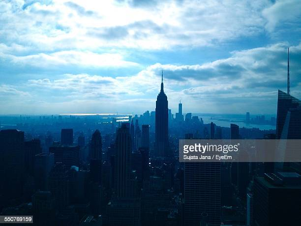High Angle View Of Silhouette Buildings Against Clouds