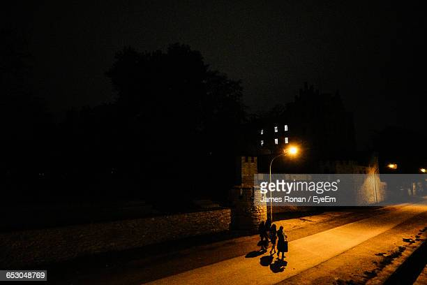 High Angle View Of Silhouette People Walking On Illuminated Street At Night