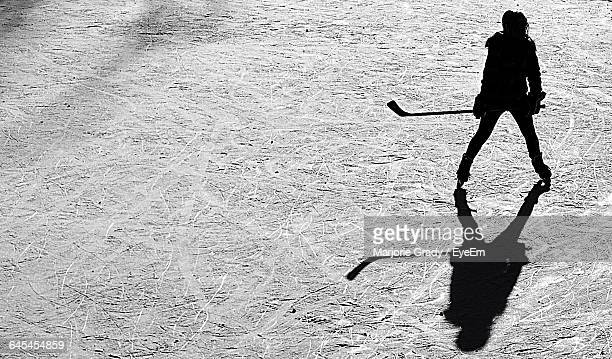High Angle View Of Silhouette Woman Playing Ice Hockey