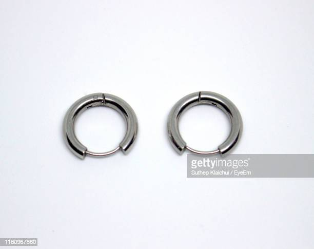 high angle view of silver earrings over white background - ohrring stock-fotos und bilder