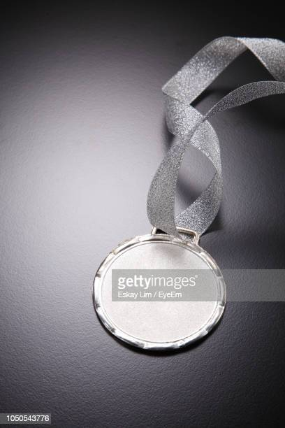 high angle view of silver medal on gray table - silver medal stock pictures, royalty-free photos & images