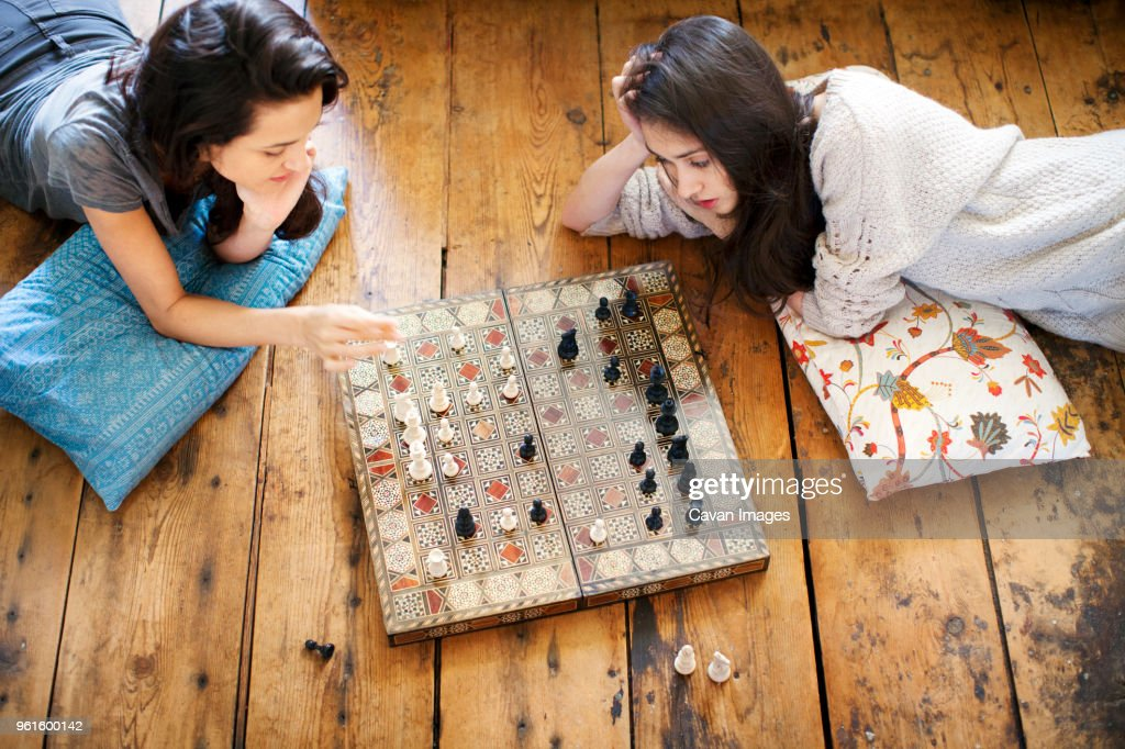 High angle view of sisters playing chess at home : Stock Photo