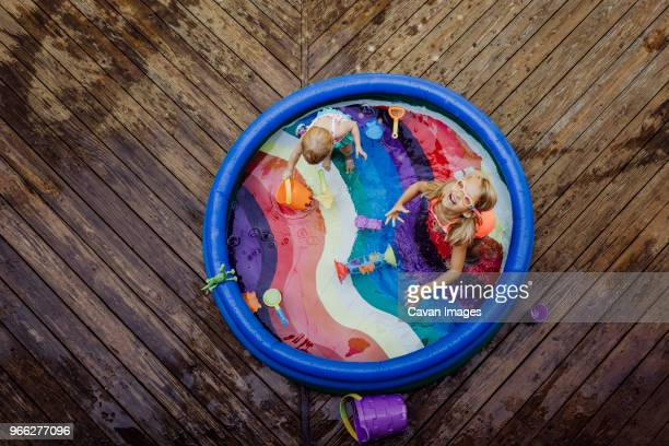 high angle view of sisters playing in wading pool on wood - circle stock pictures, royalty-free photos & images