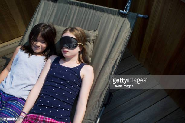 High angle view of sisters relaxing on hammock