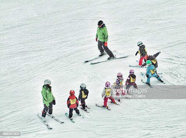 high angle view of ski instructors with students on snow - steve matten stock pictures, royalty-free photos & images