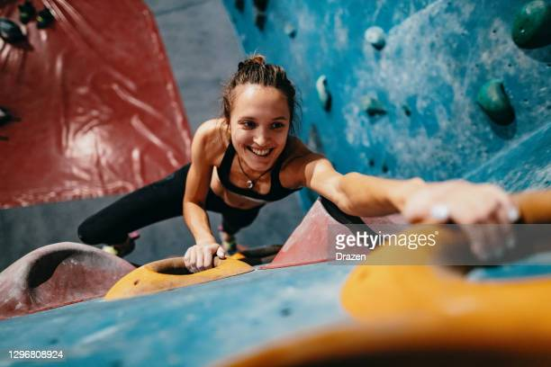 hochwinkelansicht der dünnen starken frau, die auf boulderwand klettert - sportlerin stock-fotos und bilder