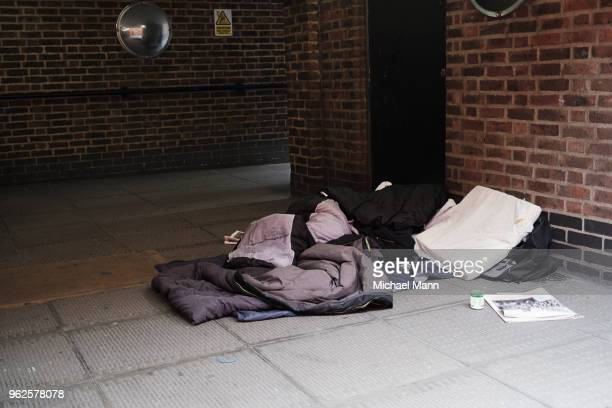 high angle view of sleeping bag on footpath by brick wall in city - homeless foto e immagini stock