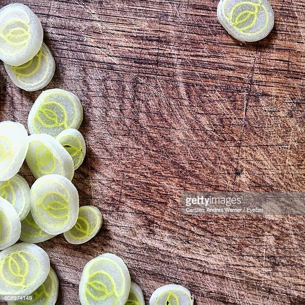 High Angle View Of Sliced Spring Onions On Wooden Table