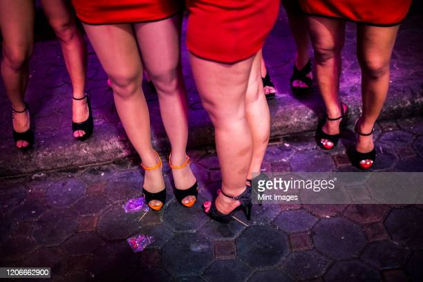 high angle view of small group of women wearing red miniskirts and high heels standing on street at night. - mini skirt stock pictures, royalty-free photos & images