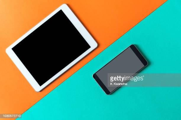 high angle view of smart phone and digital tablet over colored background - dos objetos fotografías e imágenes de stock