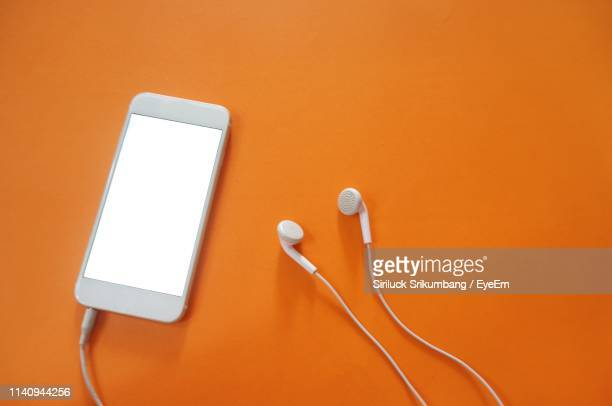high angle view of smart phone and headphones against orange background - orange background stock pictures, royalty-free photos & images