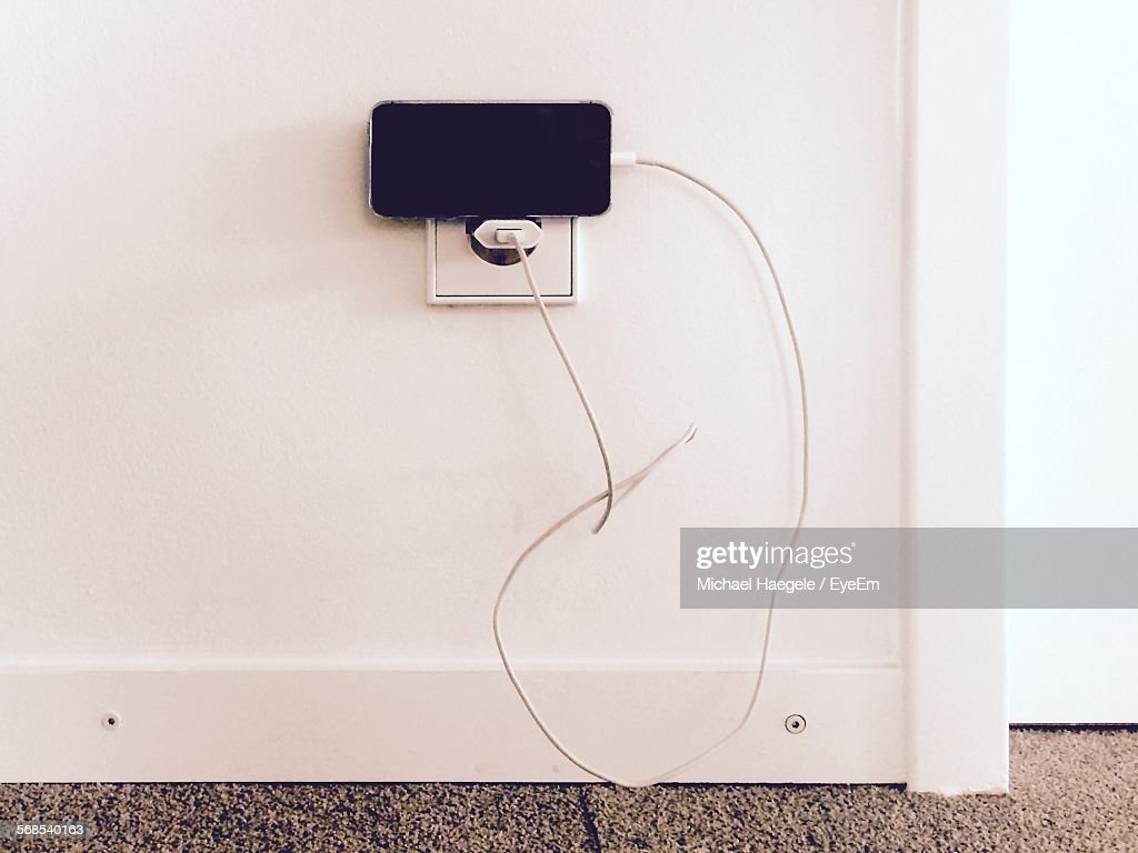 High Angle View Of Smart Phone Charging Against White Wall : Stock Photo